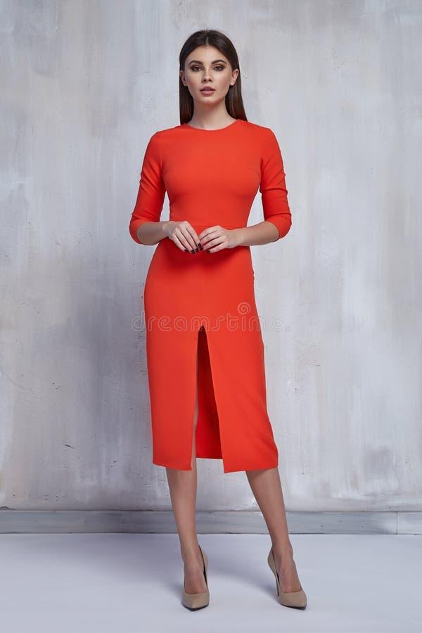 den nätta modekvinnan bär modellen för stil för partiet för hår för brunetten för den magra orange för trendkläder för klänningen arkivfoto