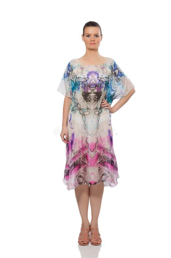 Den nätta modellen i den långa eleganta klänningen som isoleras på vit royaltyfri bild
