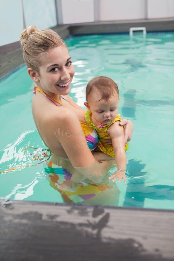 Den nätta modern och behandla som ett barn på simbassängen fotografering för bildbyråer