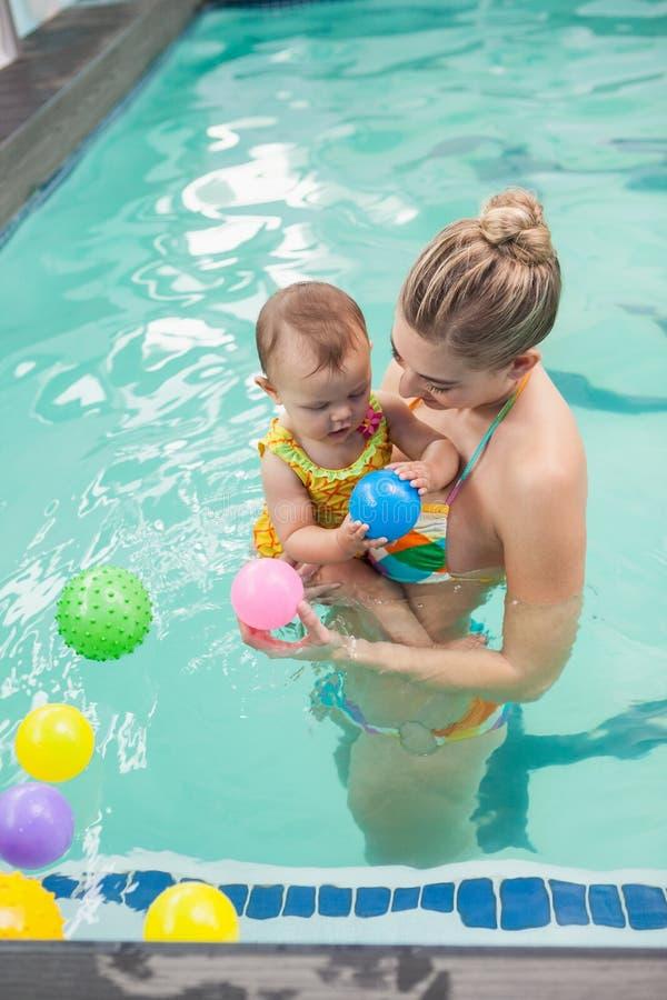 Den nätta modern och behandla som ett barn på simbassängen royaltyfria foton