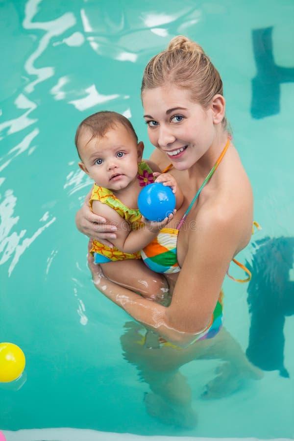Den nätta modern och behandla som ett barn på simbassängen arkivfoto