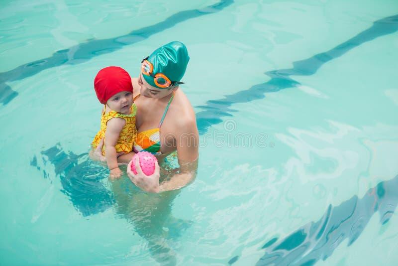 Den nätta modern och behandla som ett barn på simbassängen arkivfoton