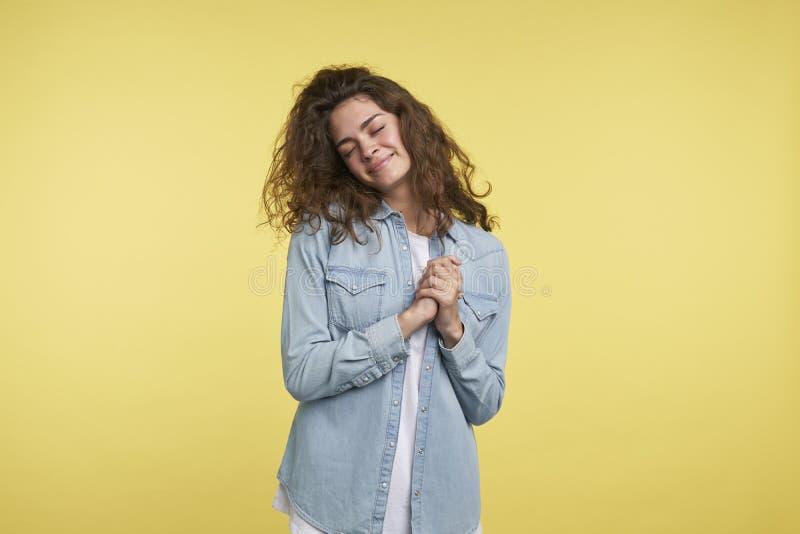 Den nätta och blyga unga brunettkvinnan med lockigt hår, är hon lycklig och glad, mot över gul bakgrund arkivbild