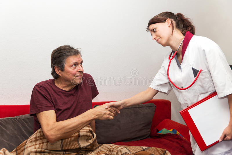 Den nätta sjuksköterskan ger pensionären en handskaka royaltyfri fotografi