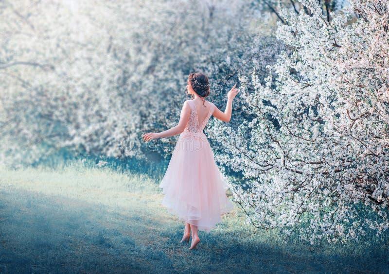 Den nätta spensliga flickan med flätat mörkt hår går, i att blomma trädgården barfota, prinsessan, går till solen, dam i delikat fotografering för bildbyråer