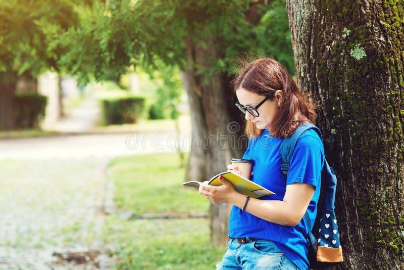 Den nätta studentflickan i exponeringsglas, läser anteckningsboken, dricker kaffe i universitetsområde parkerar Sommarferier, utb arkivfoton