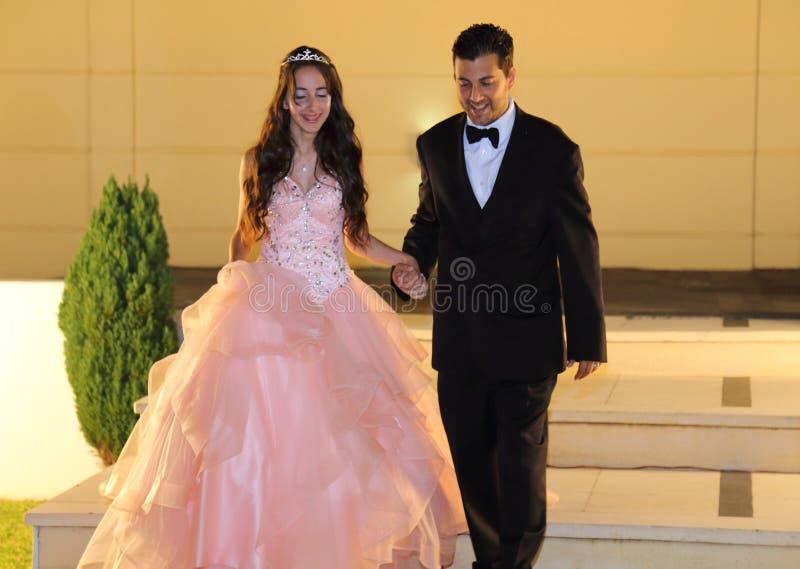 Den nätta tonåriga quinceanerafödelsedagflickan som firar i prinsessaklänningrosa färger, festar, special beröm av den passande k royaltyfria foton