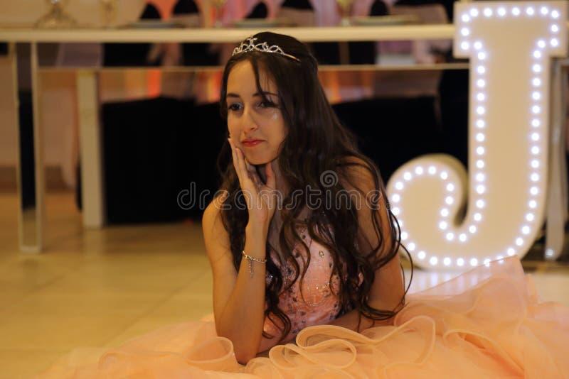 Den nätta tonåriga quinceanerafödelsedagflickan som firar i prinsessaklänningrosa färger, festar, special beröm av den passande k royaltyfria bilder