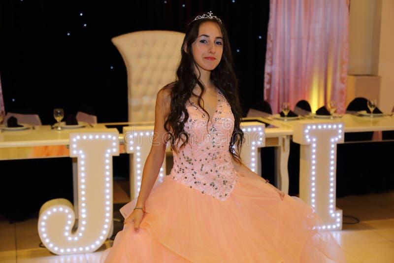 Den nätta tonåriga quinceanerafödelsedagflickan som firar i prinsessaklänningrosa färger, festar, special beröm av den passande k royaltyfri foto