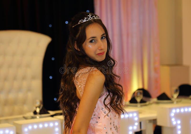 Den nätta tonåriga quinceanerafödelsedagflickan som firar i prinsessaklänningrosa färger, festar, special beröm av den passande k royaltyfri bild
