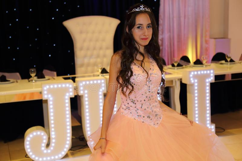 Den nätta tonåriga quinceanerafödelsedagflickan som firar i prinsessaklänningrosa färger, festar, special beröm av den passande k arkivbild