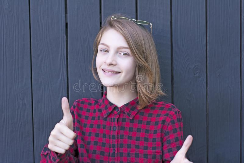 Den nätta tonårs- flickan som främjar något med tummar gör en gest upp arkivbilder
