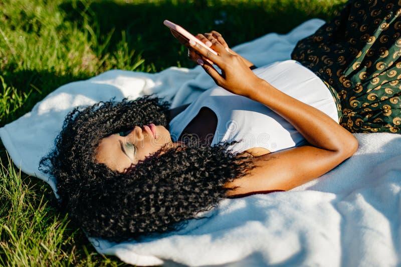 Den nätta unga afrikanska flickan är avslappnande på gräset Hon är smsa och bläddra via mobiltelefonen Ovanför ståenden royaltyfri fotografi