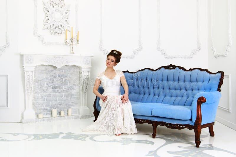 Den nätta unga bruden i den vita klänningen sitter på den barocka soffan royaltyfri bild