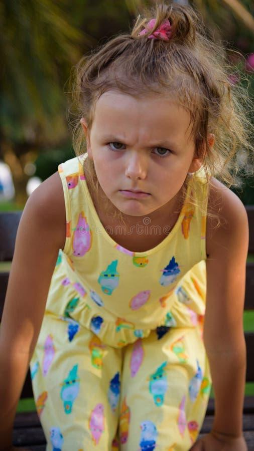 Den nätta unga eurupean flickan som ser ilsken eller uppriven, sitter på bänken i parkera 3 arkivbild
