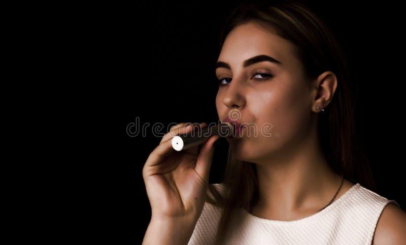 Den nätta unga flickan använder den elektroniska cigaretten royaltyfri bild
