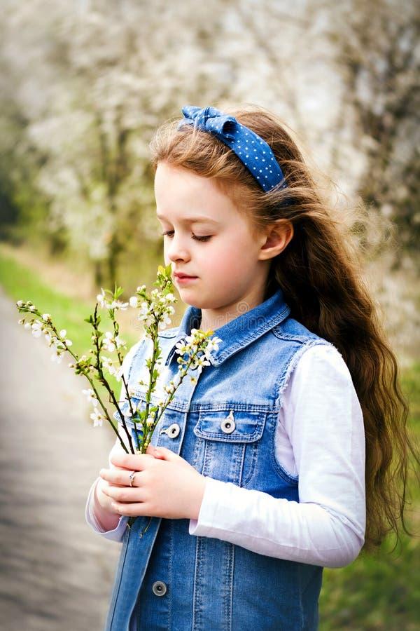 Den nätta unga flickan i blomma parkerar arkivbild