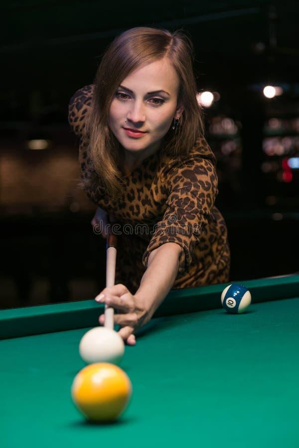 Den nätta unga flickan spelar billiard arkivfoton