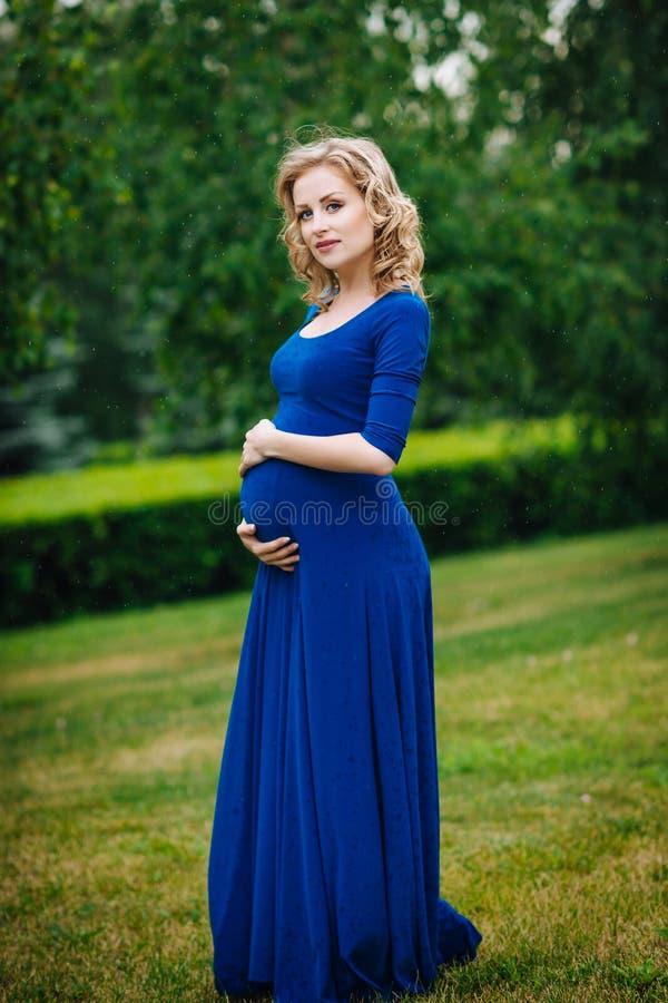 Den nätta unga gravida kvinnan i blått klär med långt blont lockigt hår som rymmer hennes buk, och se kameran i sommar parkera royaltyfri foto