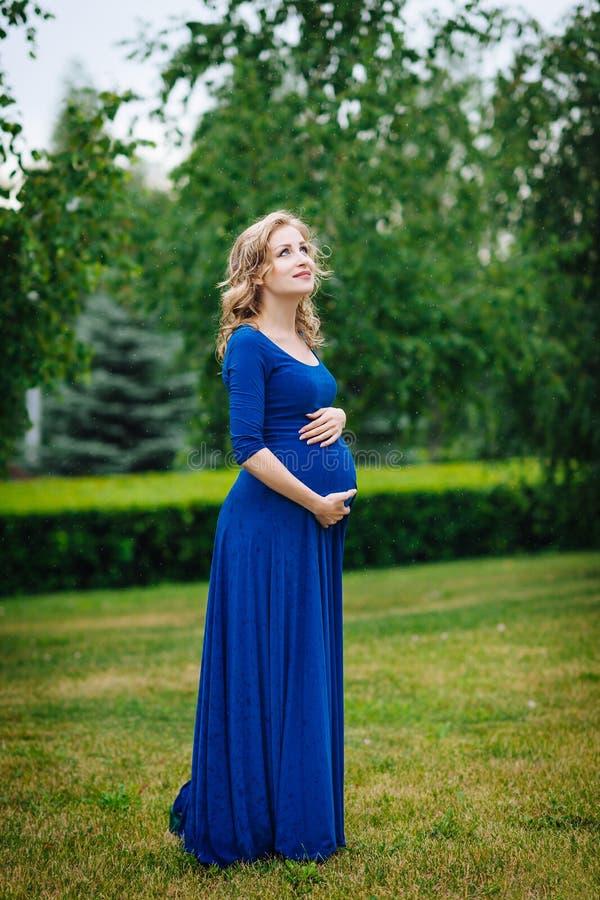 Den nätta unga gravida kvinnan i blått klär med långt blont lockigt hår som rymmer hennes buk som ler, och se himmel i sommar par royaltyfria bilder