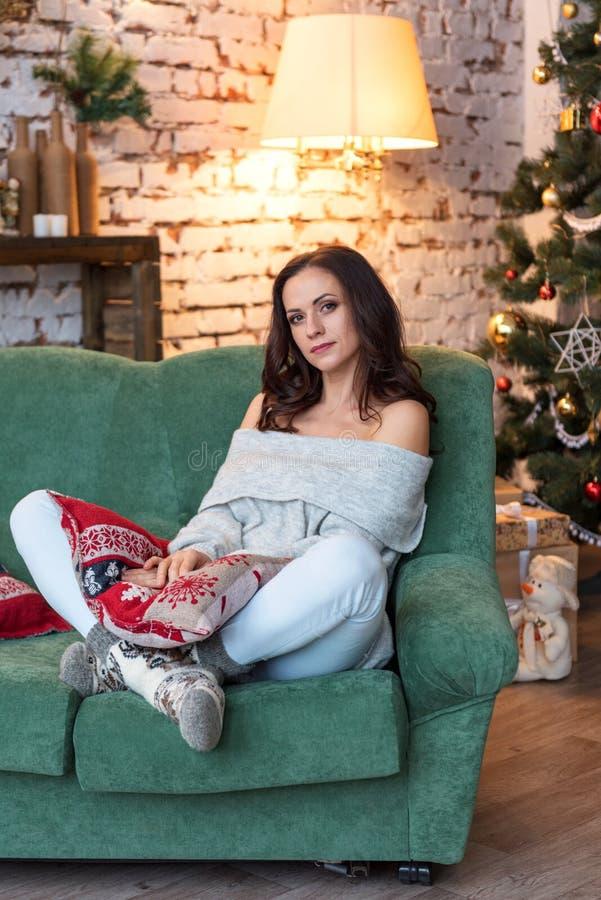 Den nätta unga kvinnan i en hemtrevlig tröja sitter på en ljus soffa i nytt års dekorerade rum fotografering för bildbyråer