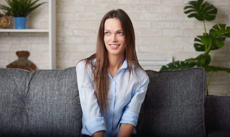 Den nätta unga kvinnan ler sammanträde på en soffa arkivfoto