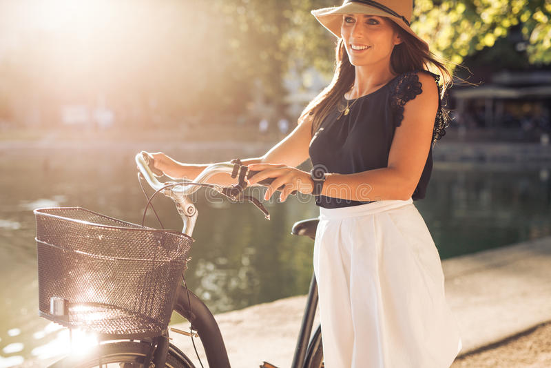 Den nätta unga kvinnan med en cykel parkerar in arkivfoto