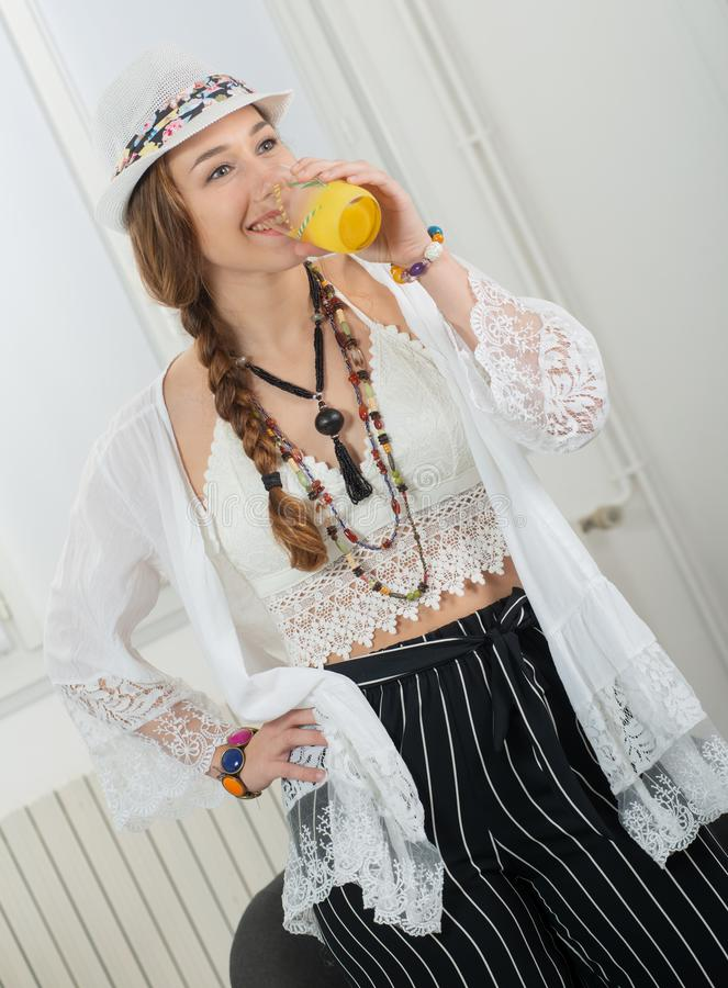 Den nätta unga kvinnan med en sommarhatt dricker exponeringsglas av orange fruktsaft arkivfoto