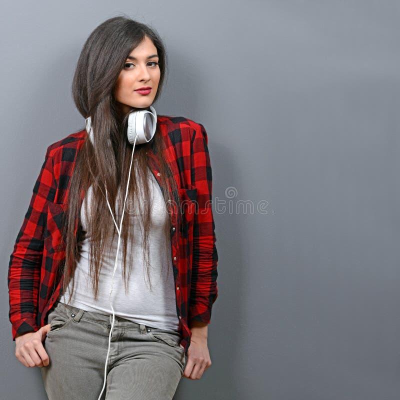 Den nätta unga kvinnan med hörlurar tycker om musiken som lutas på den gråa väggen royaltyfria bilder