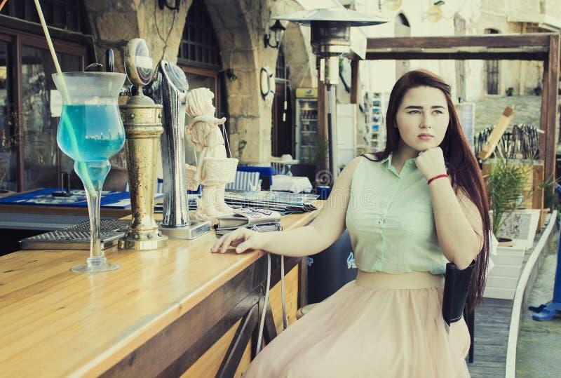 den nätta unga kvinnan med mörk lång hår- och blåtteyesl sitter på a royaltyfri fotografi
