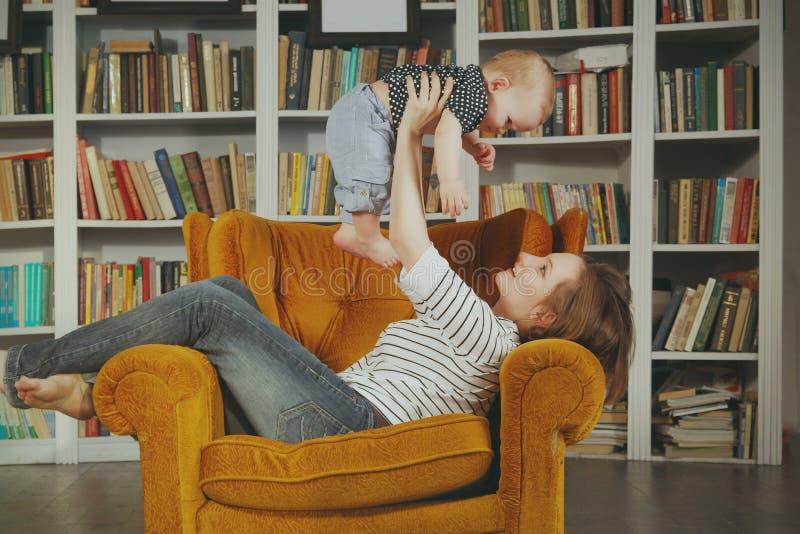 Den nätta unga kvinnan och hon behandla som ett barn barnet spelar inre rum mot bokhyllor royaltyfria bilder