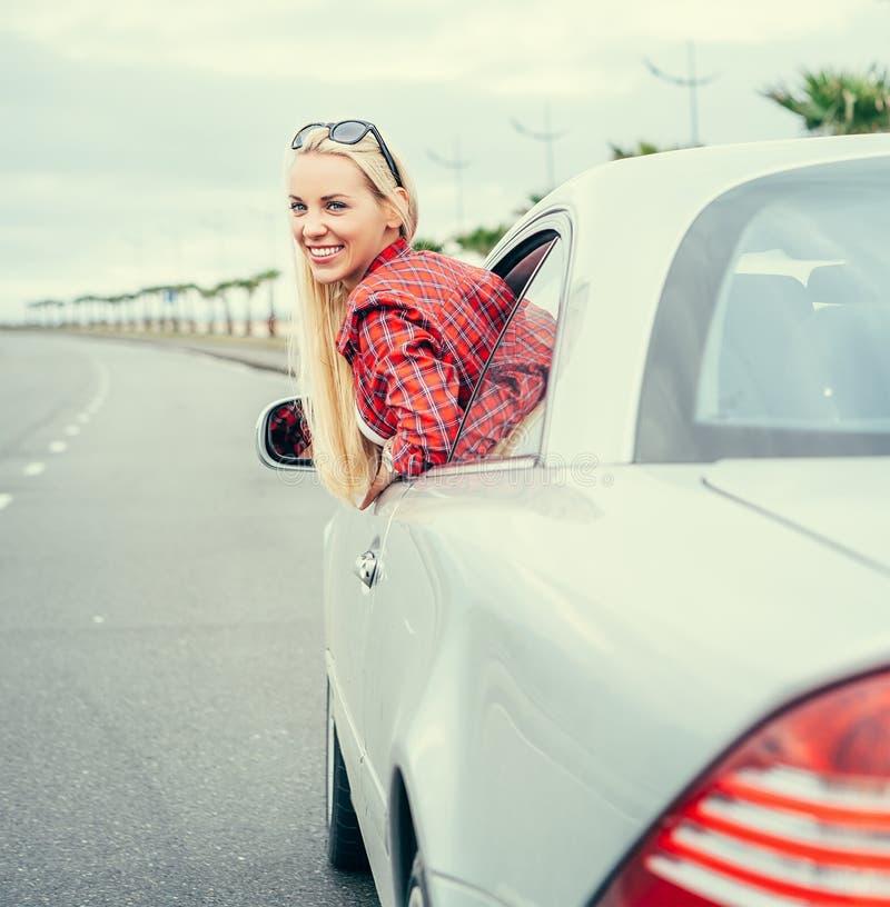Den nätta unga kvinnan ser ut från bilen royaltyfria bilder
