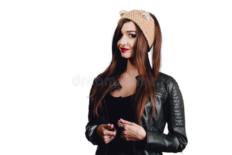 Den nätta unga kvinnan som bär en hand, stack den beigea hatten på vit bakgrund isolerat Härlig flicka in med öraklaffen, royaltyfri fotografi