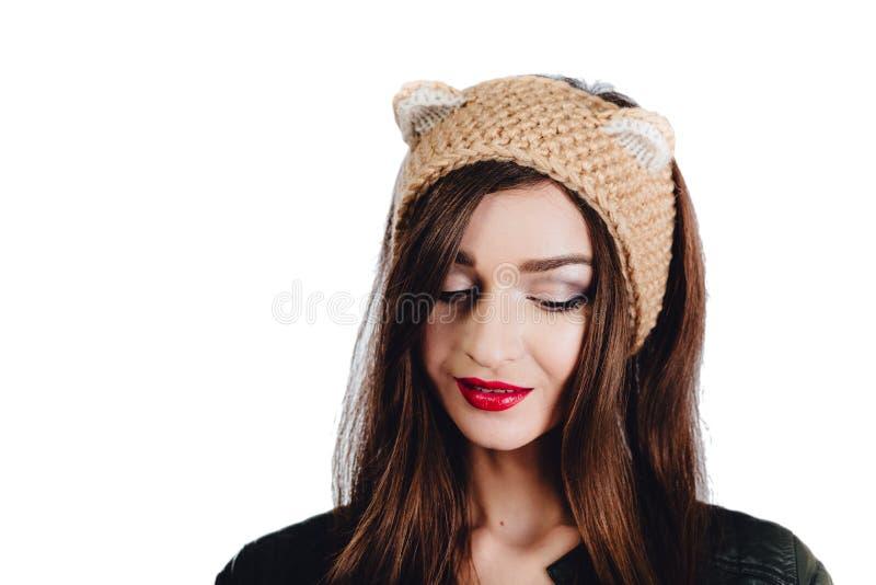 Den nätta unga kvinnan som bär en hand, stack den beigea hatten på vit bakgrund isolerat Härlig flicka in med öraklaffen, arkivfoto