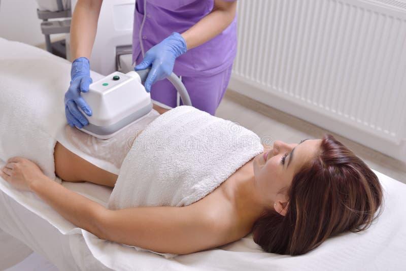 Den nätta unga kvinnan som får cryolipolyse fet behandling låtsas in arkivbilder