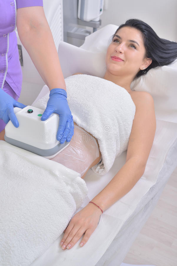 Den nätta unga kvinnan som får cryolipolyse fet behandling låtsas in royaltyfri foto