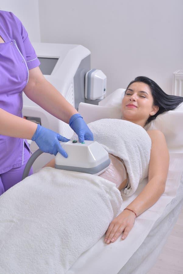 Den nätta unga kvinnan som får cryolipolyse fet behandling låtsas in arkivfoto
