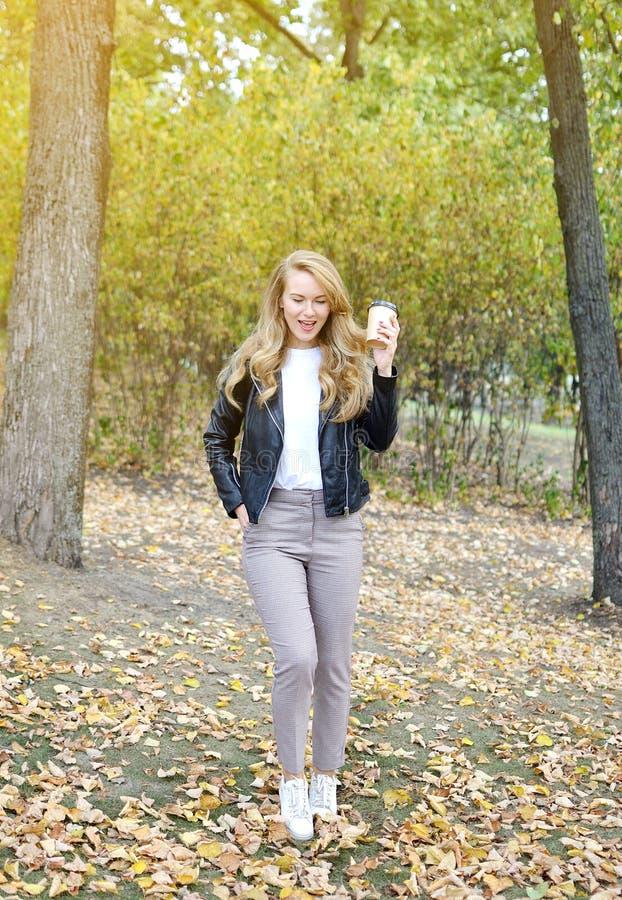 Den nätta unga kvinnan som går i Autumn Park Relax Drinking Coffee, tar den bort koppen royaltyfri fotografi