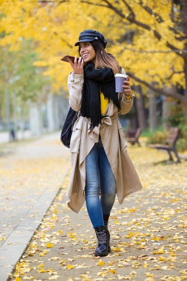 Den nätta unga kvinnan som talar med händer som är fria av mobiltelefonen, medan gå till och med, parkerar i höst royaltyfria foton