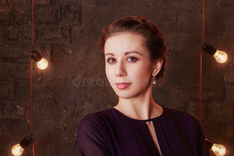 Den nätta unga kvinnan står i studio med tegelstenväggen arkivbild