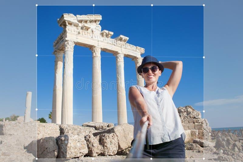 Den nätta unga kvinnan tar ett självfoto på den antika tempelsikten fotografering för bildbyråer