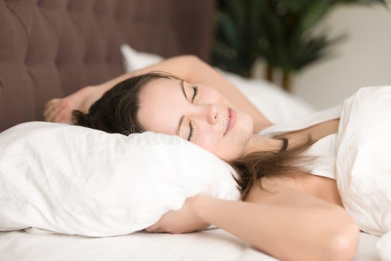 Den nätta unga kvinnan tycker om lång sömn i säng arkivfoto