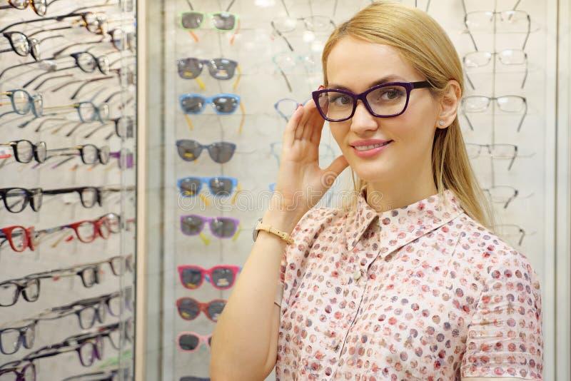 Den nätta unga kvinnan väljer exponeringsglas i optikerlager arkivfoto