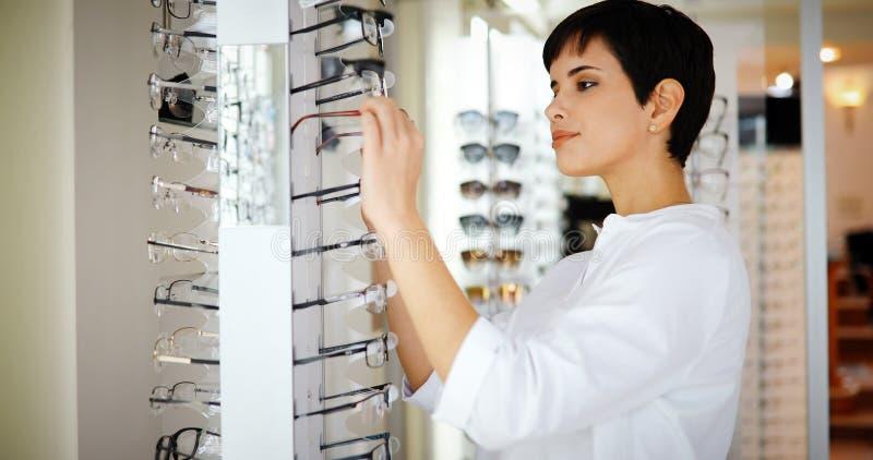 Den nätta unga kvinnan väljer nya exponeringsglas på optiklagret royaltyfri foto