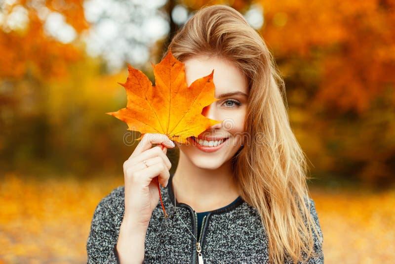 Den nätta unga lyckliga unga kvinnan i stilfull kläder med ett härligt leende rymmer i hennes hand ett höstguld-guling blad nära  royaltyfria bilder