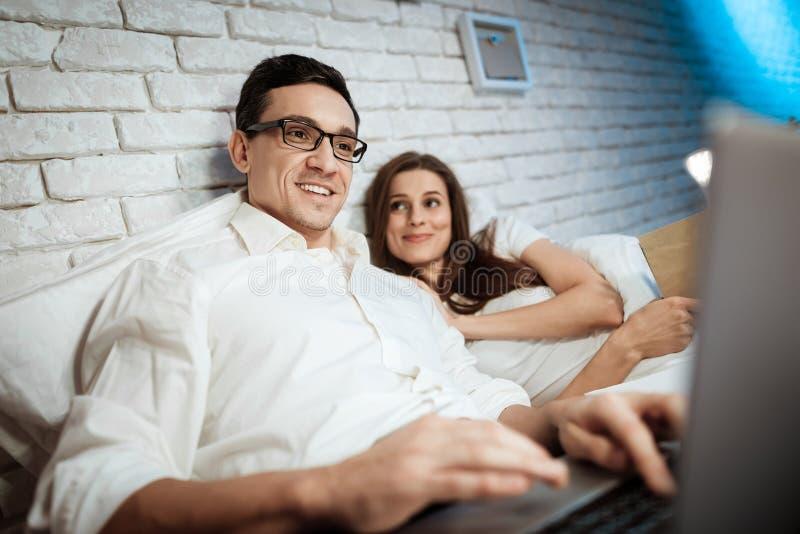Den nöjda affärsmannen skriver på bärbara datorn Den unga kvinnan ligger i säng med affärsmannen royaltyfria foton