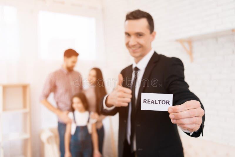 Den nöjda mannen i dräkt rymmer kortet med inskriften vid fastighetsmäklare house försäljningen royaltyfria foton