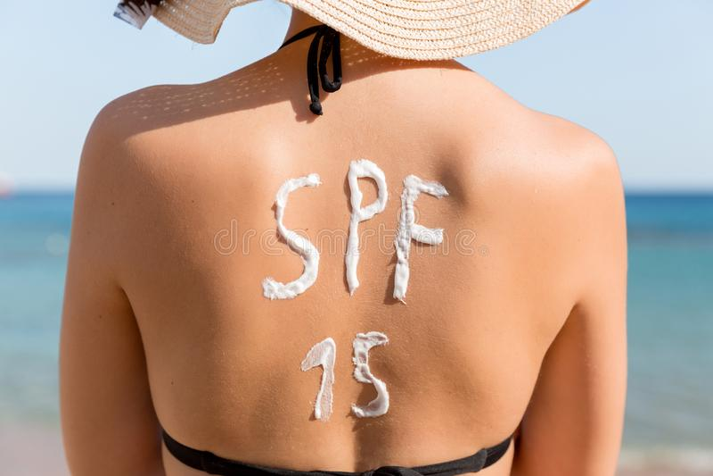 Den n?tta kvinnan har ord f?r spf 15 gjorde av solkr?m p? hennes baksida p? stranden royaltyfria bilder