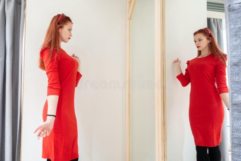 Den n?tta kvinnan som f?rs?ker p? kl?der i ett passande, shoppar damen i den r?da kl?nningen reflekteras i spegeln royaltyfri foto