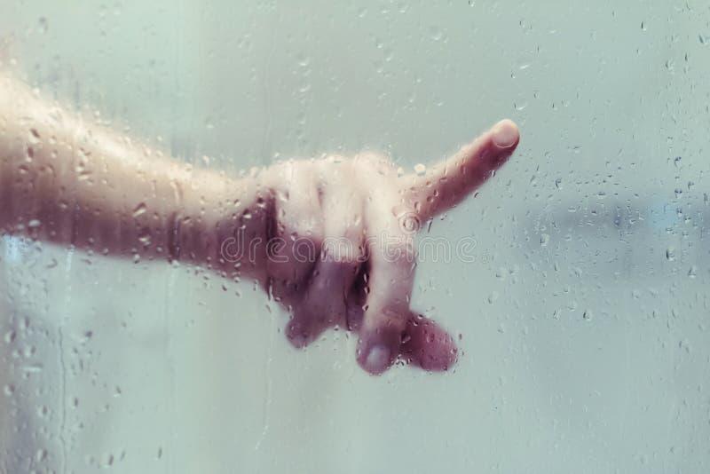 Den nakna härliga kvinnan som tar en dusch, och handlag räcker vått misted exponeringsglas royaltyfria bilder